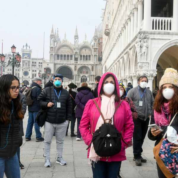Tourists wearing protective masks visit Venice, Italy on Feb. 25, 2020, during the usual period of the Carnival festivities which have been cancelled following an outbreak of the COVID-19 novel coronavirus in northern Italy. (ANDREA PATTARO/AFP via Getty Images)