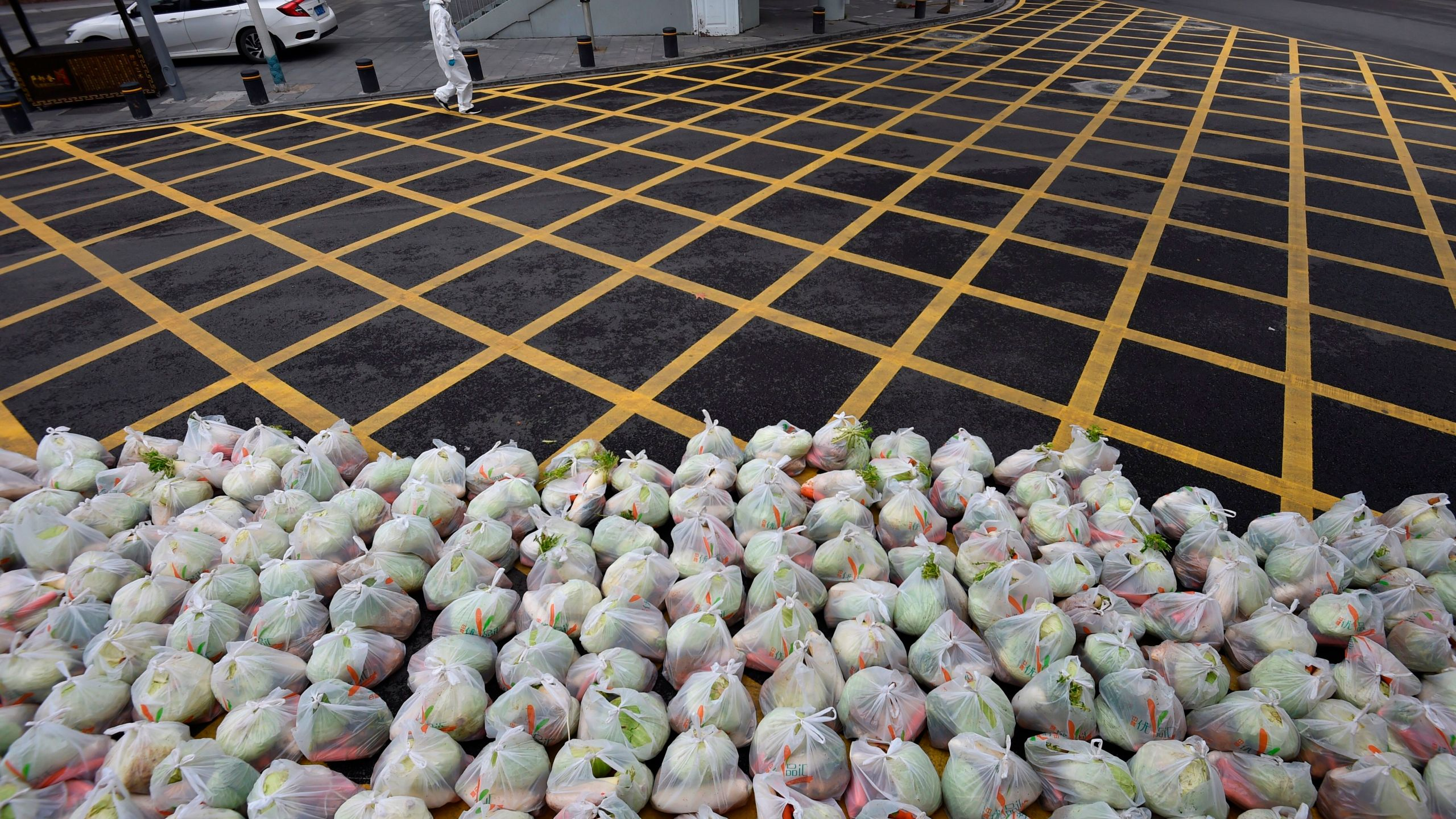 A man wearing protective clothing as a preventive measure against the COVID-19 coronavirus walks past bags of vegetables being prepared for delivery on an almost empty street in Wuhan, in China's central Hubei province on Feb. 26, 2020. (Credit: STR/AFP via Getty Images)