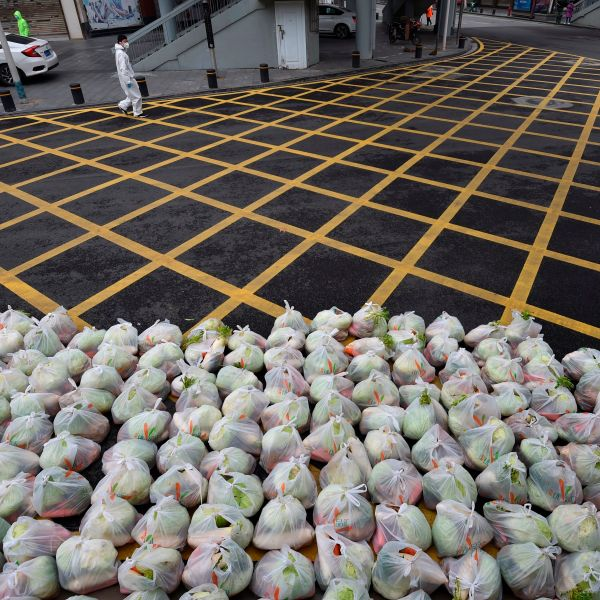 A man wearing protective clothing as a preventive measure against the COVID-19 coronavirus walks past bags of vegetables being prepared for delivery on an almost empty street in Wuhan, in China's central Hubei province on Feb. 26, 2020. (STR/AFP via Getty Images)