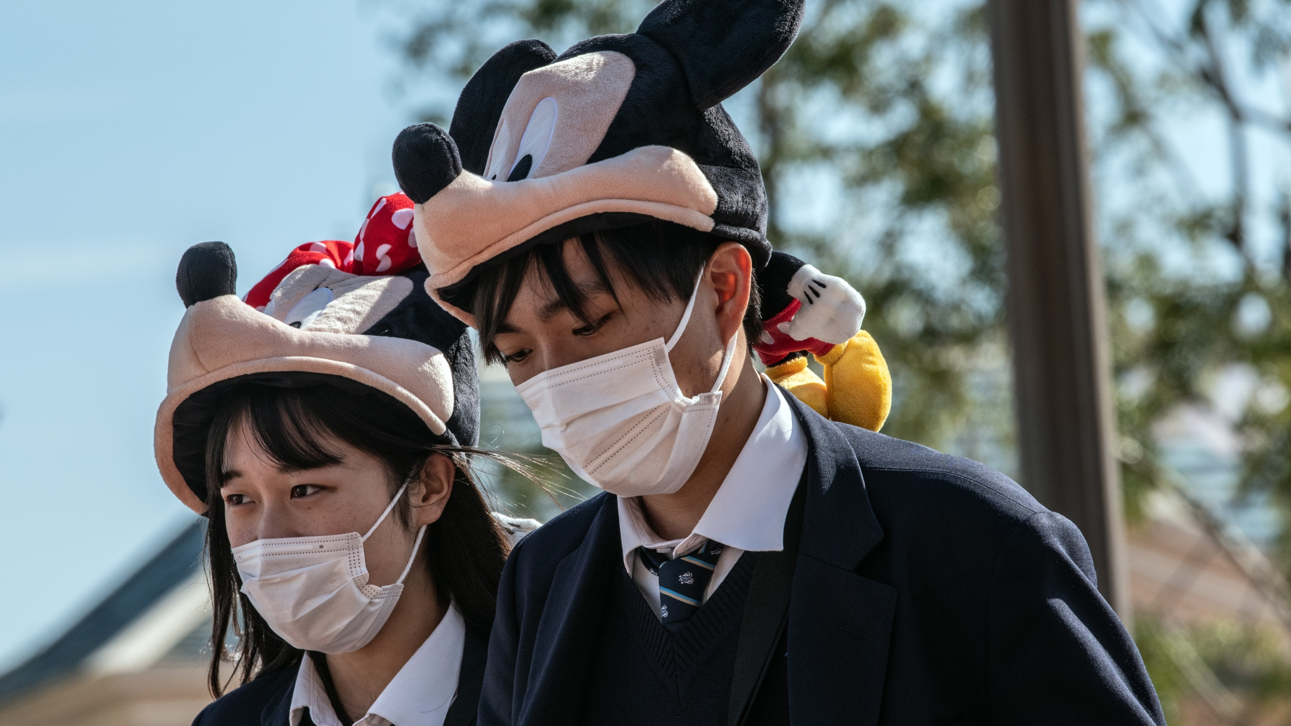Students wearing Disney character hats and face masks leave Tokyo Disneyland on the day it announced it will close until March 15th because of concerns over the Covid-19 virus, on Feb. 28, 2020. (Carl Court/Getty Images)