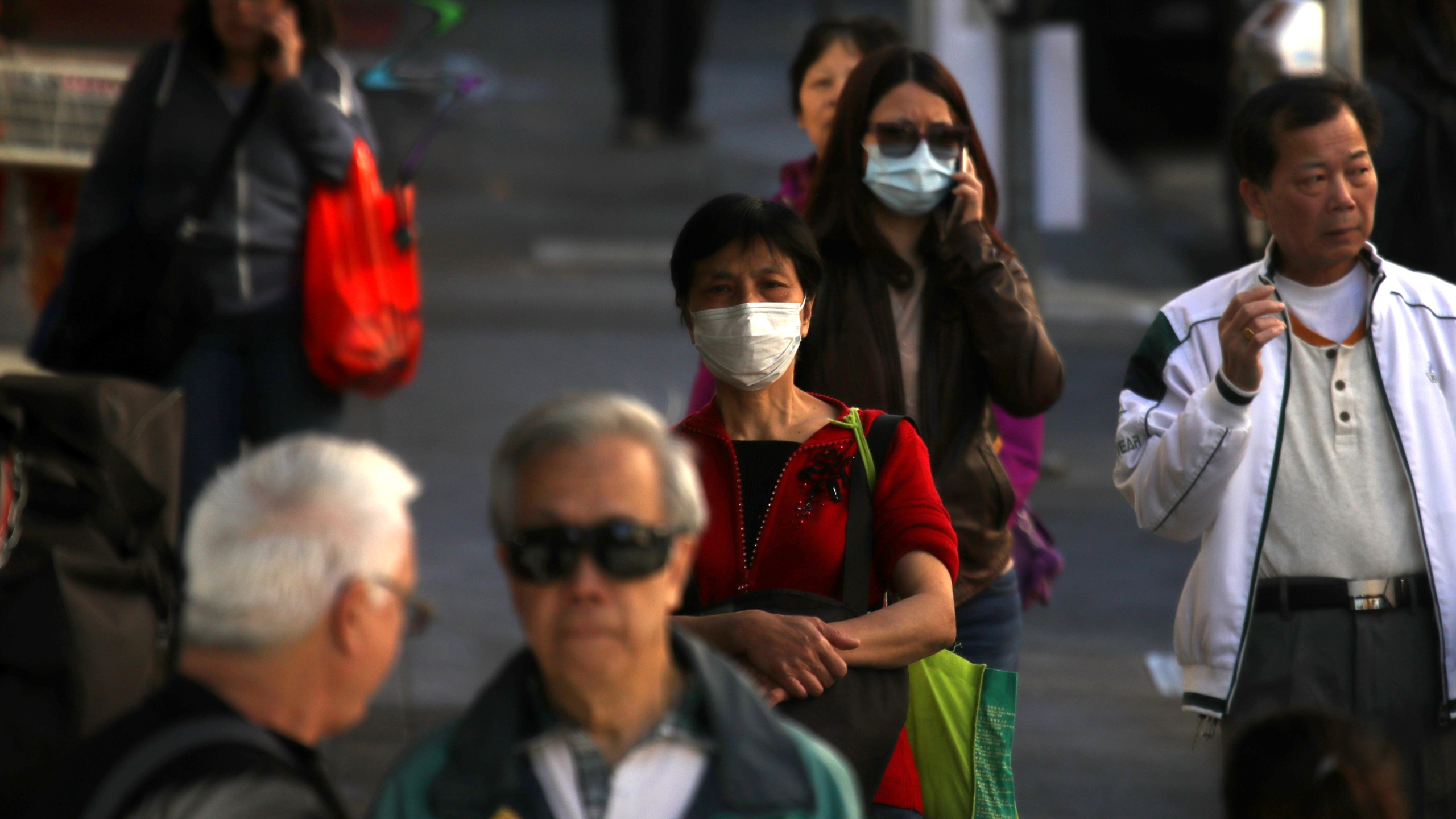 People wear surgical masks as they walk along Grant Avenue in San Francisco's Chinatown on Feb. 26, 2020. (Credit: Justin Sullivan / Getty Images)