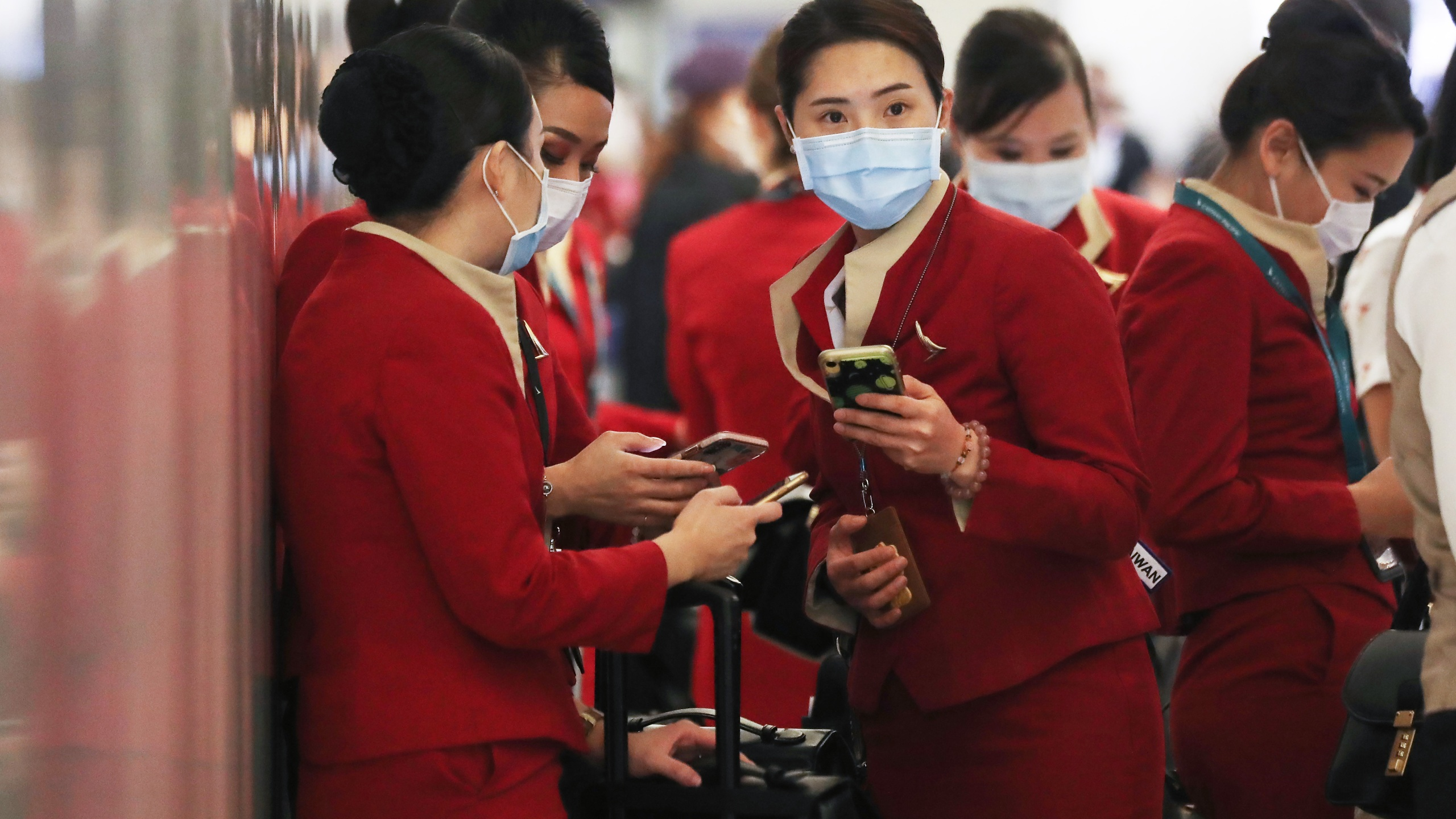 A flight crew from Cathay Pacific Airways, wearing protective masks, stand in the international terminal at Los Angeles International Airport after arriving on a flight from Hong Kong on Feb. 28, 2020. (Credit: Mario Tama / Getty Images)