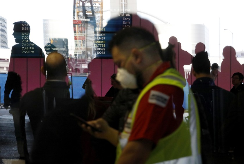 An airport worker wears a mask amid fears of coronavirus at the Tom Bradley International Terminal at Los Angeles International Airport on Feb. 8. (Genaro Molina / Los Angeles Times)