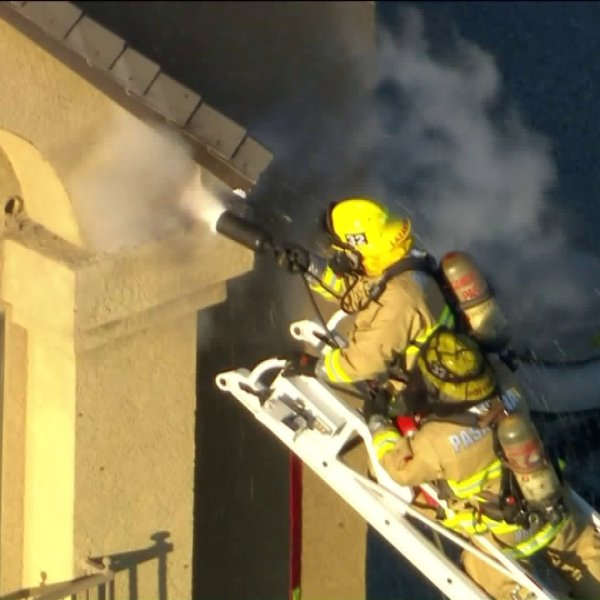 Firefighters work to remove a bee hive at 1599 East Colorado Blvd. atop Howard Johnson Inn in Pasadena. (Credit KTLA)