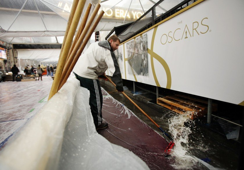 In 2014, a worker tries to clears the Oscars red carpet of rainwater outside the Dolby Theater in Hollywood. (Credit: Al Seib / Los Angeles Times)