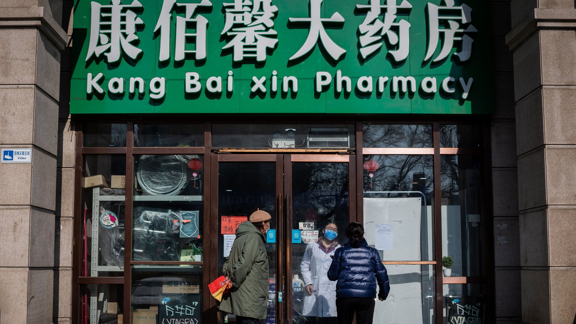 People wearing protective face masks and gloves stand outside a closed off Pharmacy as they try to get face masks, gloves and hand sanitizer gel in Beijing on February 15, 2020. (Credit: Nicolas Asfouri/AFP/Getty Images)