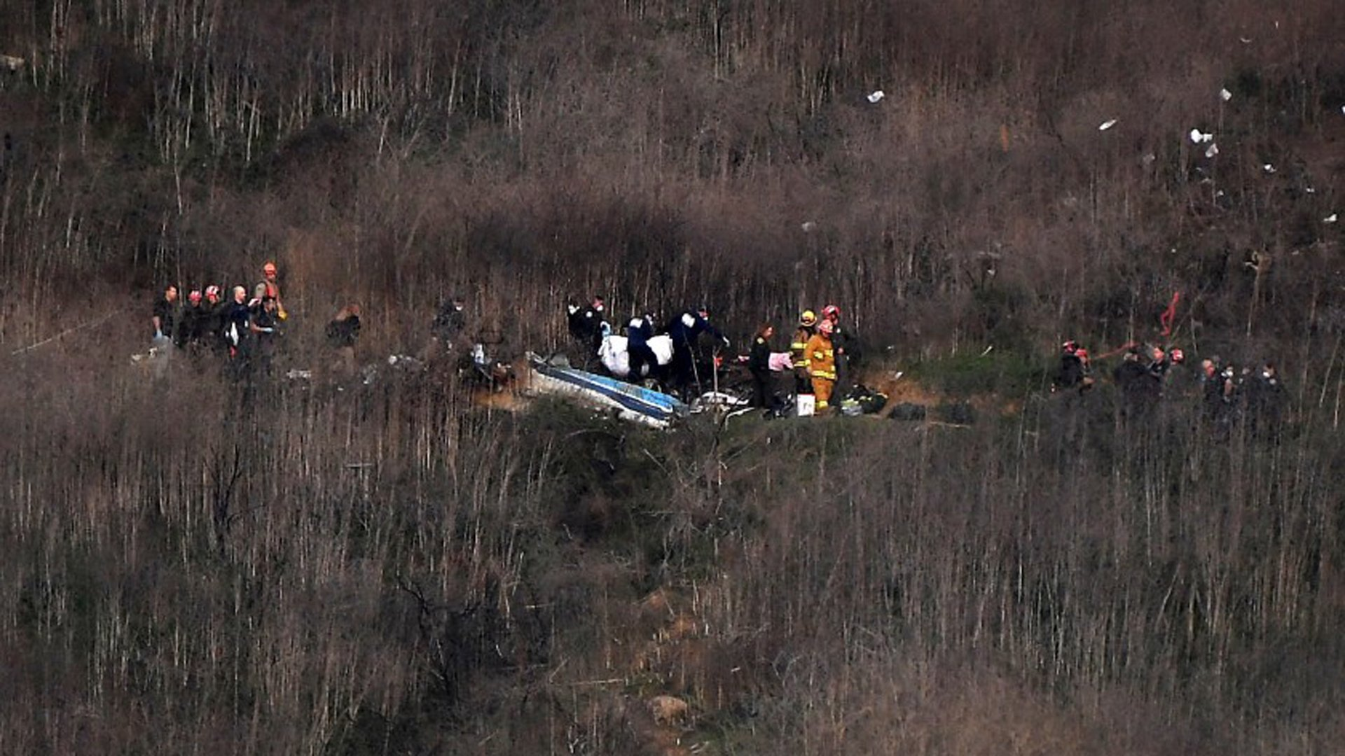 Officials remove a body from the wreckage in Calabasas where Kobe Bryant and his daughter Gianna were among nine dead in a helicopter crash. (Christina House / Los Angeles Times)
