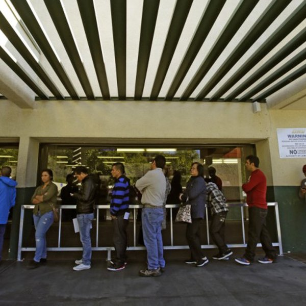 People stand at a DMV office in Los Angeles in 2014. (Credit: Irfan Khan / Los Angeles Times)