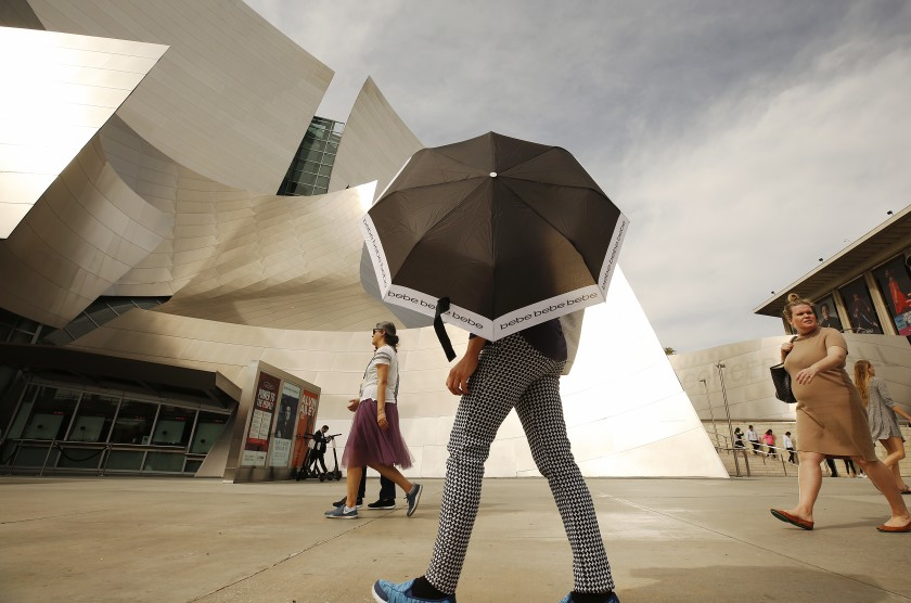 A person uses an umbrella for shade in downtown Los Angeles on Feb. 27, 2020. (Credit: Al Seib / Los Angeles Times)