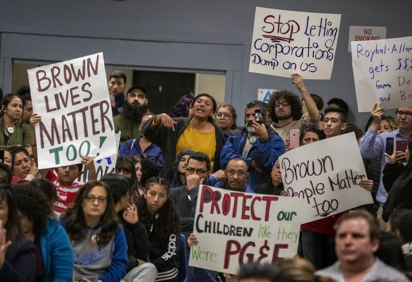 Residents hold signs during a town hall meeting in Cudahy in January 2020 after a Delta Air Lines jet dumped fuel over multiple L.A. County suburbs. (Credit: Brian van der Brug / Los Angeles Times)