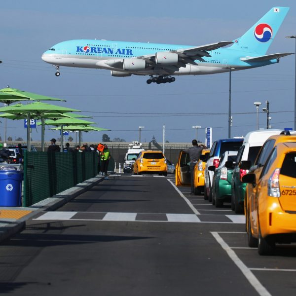 A Korean Air plane lands as taxis are lined up at the new 'LAX-it' ride-hail passenger pickup lot at Los Angeles International Airport on Nov. 6, 2019. (Credit: Mario Tama/Getty Images)