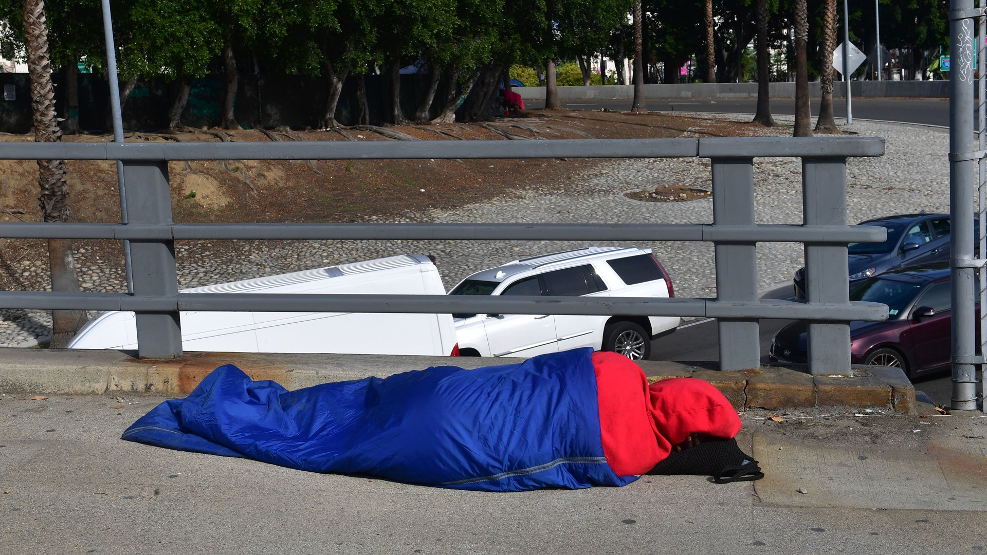 A homeless person sleeps on the street in Los Angeles on Dec. 17, 2019. (Credit: Frederic J. Brown / AFP / Getty Images)