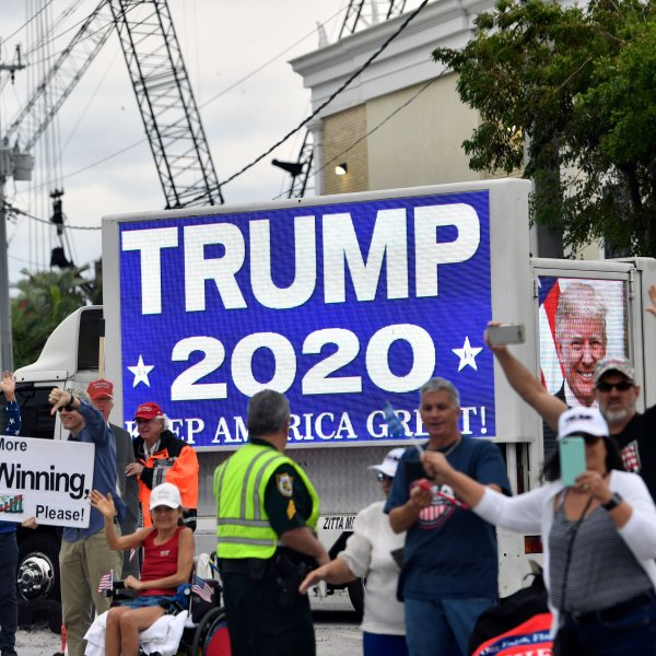 Supporters wave as Donald Trump's motorcade drives past near Mar-a-Lago in West Palm Beach, Florida on Dec. 24, 2019. (Credit: NICHOLAS KAMM/AFP via Getty Images)