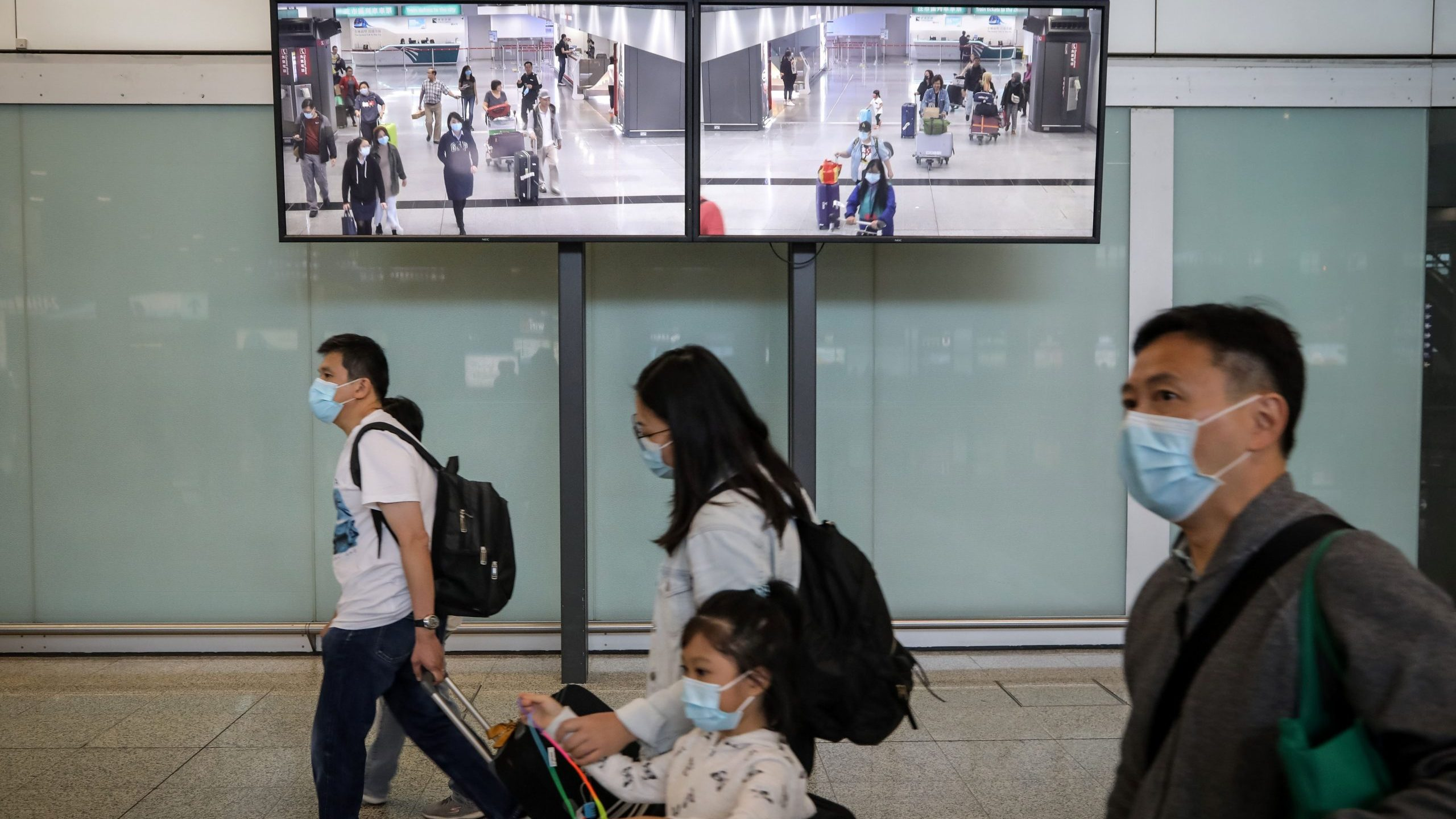 Travelers wearing face masks as a precautionary measure walk in the arrivals area at Hong Kong International Airport ahead of the Chinese New Year in Hong Kong on Jan. 23, 2020. (Credit: VIVEK PRAKASH/AFP via Getty Images)
