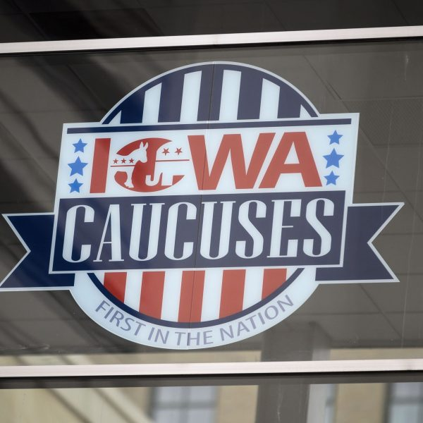 A sign for the Iowa caucuses hangs in downtown Des Moines, Iowa, on Jan. 25, 2020. (Credit: STEPHEN MATUREN/AFP via Getty Images)