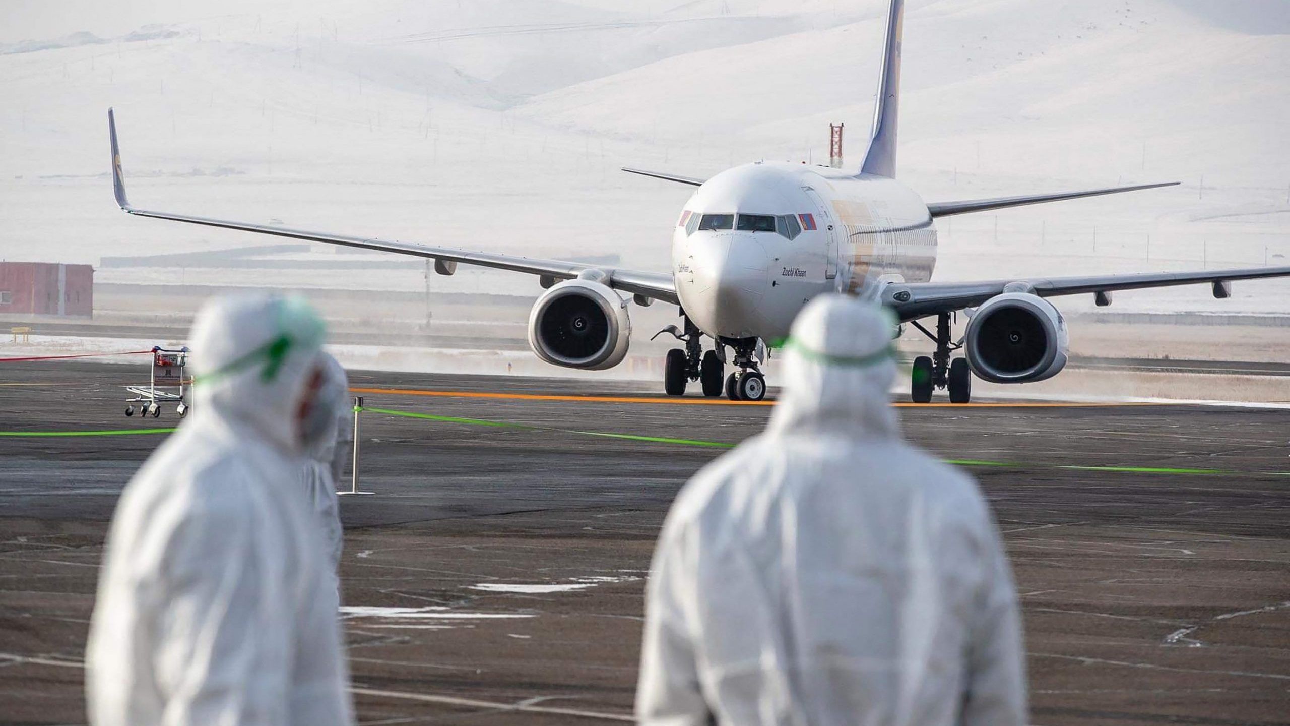 Staff wearing protective suits watch as a plane carrying evacuees from Wuhan arrives in Mongolia on Feb.1, 2020, amid the coronavirus outbreak in China. (Credit: Byambasuren Byamba-Ochir/AFP via Getty Images)