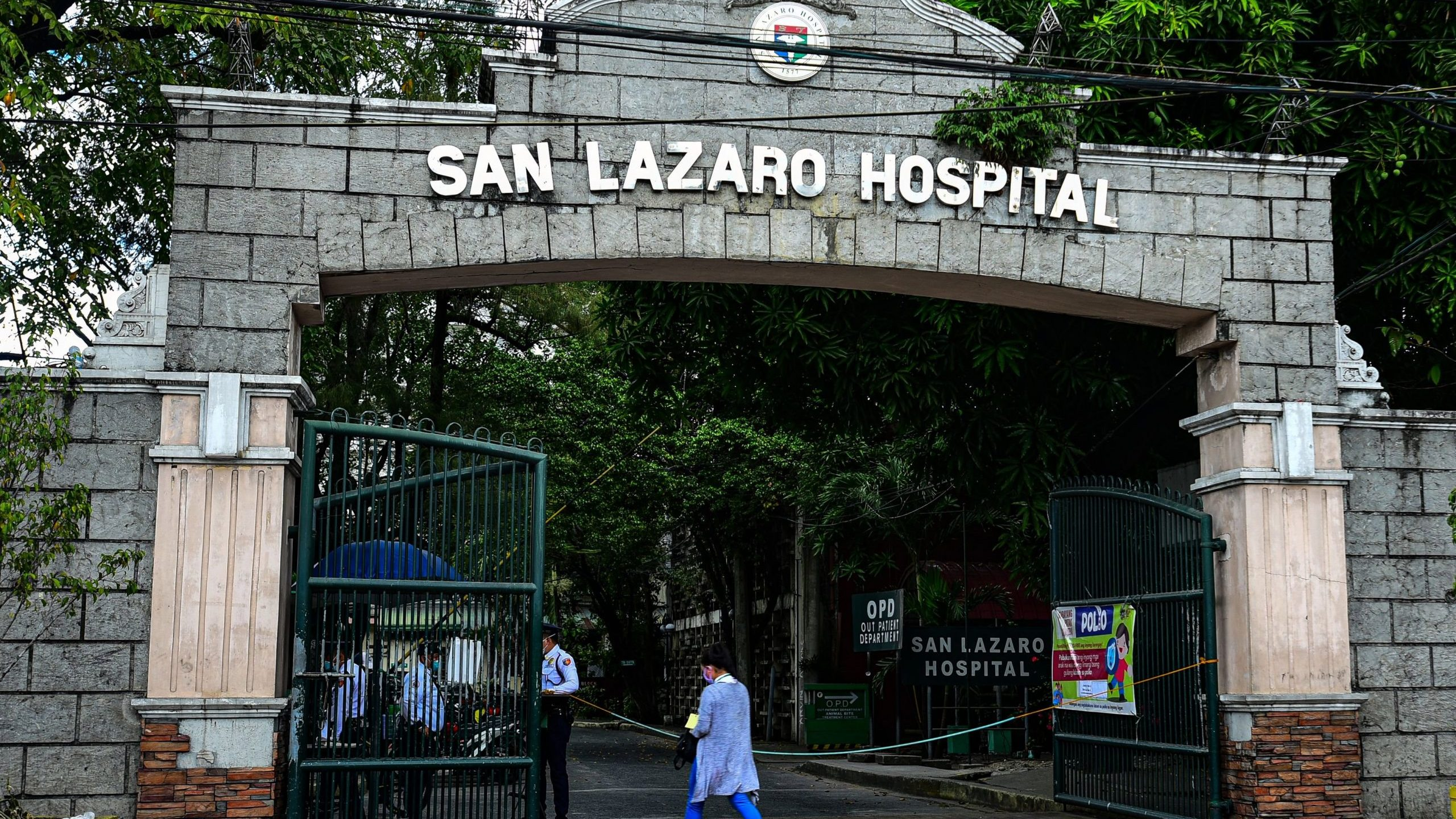 People wearing face masks walk past the main gates of the San Lazaro Hospital in Manila on Feb. 2, 2020. (Credit: MARIA TAN/AFP via Getty Images)