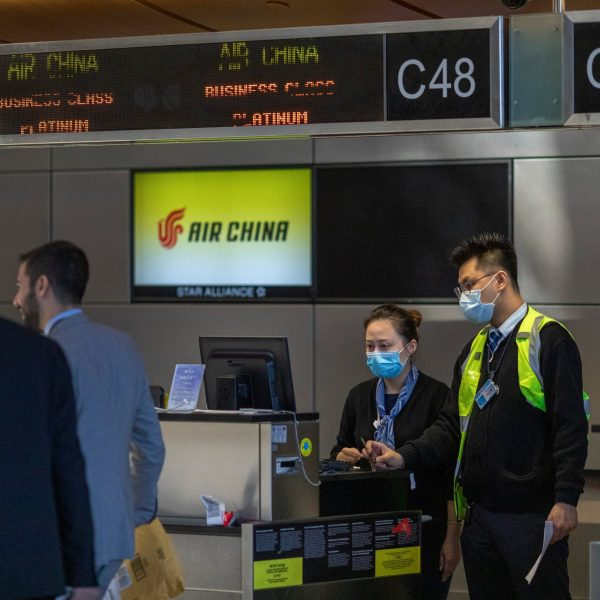 Air China employees wear medical masks for protection against the novel coronavirus outbreak at LAX Tom Bradley International Terminal on February 2, 2020 in Los Angeles, California. (Credit: David McNew/Getty Images)