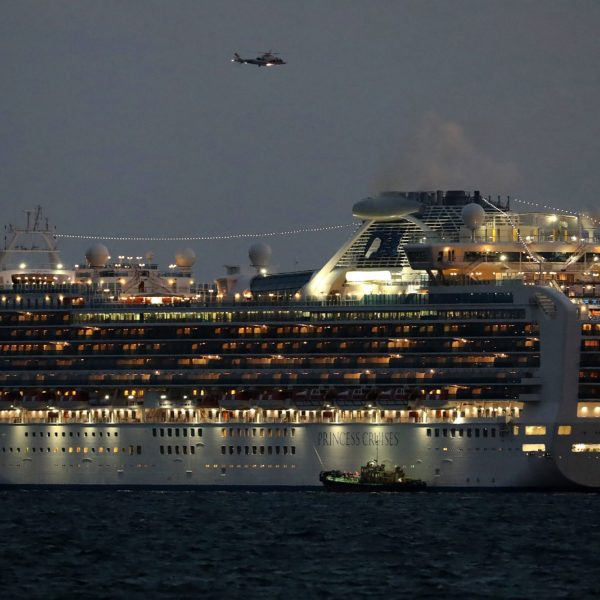 A small boat is pictured next to the Diamond Princess cruise ship with over 3,000 people as it sits anchored in quarantine off the port of Yokohama on Feb. 4, 2020, a day after it arrived with passengers feeling ill. (Credit: STR/JIJI PRESS/AFP via Getty Images)