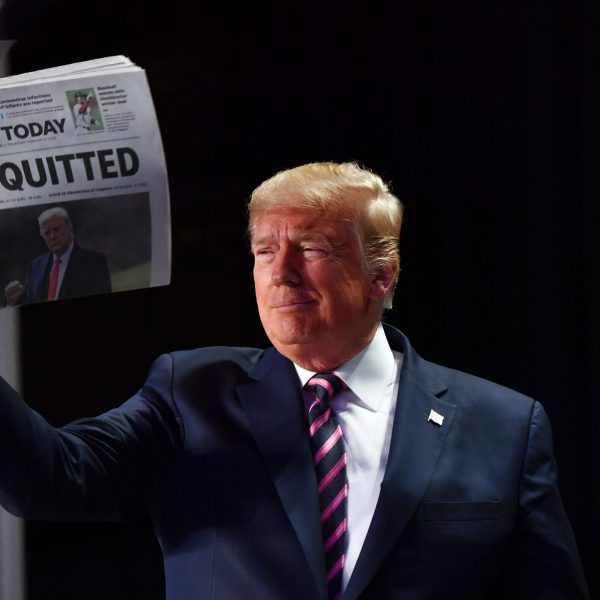 """President Donald Trump holds up a newspaper with the headline that reads """"ACQUITTED"""" at the 68th annual National Prayer Breakfast, at the Washington Hilton on Feb. 6, 2020, in Washington.(Credit: NICHOLAS KAMM/AFP via Getty Images)"""
