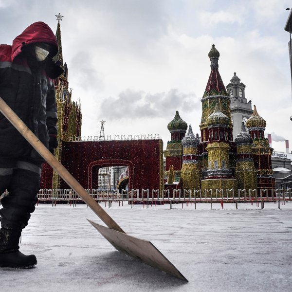 A municipal worker wearing a face mask cleans the snow in front of a model of Saint Basil cathedral, in Moscow, on Feb. 7, 2020. (Credit: ALEXANDER NEMENOV/AFP via Getty Images)