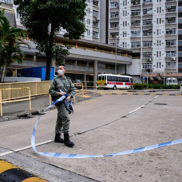 Police officers wearing face masks stand guard in front of a cordon outside Hong Mei House at the Cheung Hong Estate in Hong Kong on February 11, 2020. (Credit: ANTHONY WALLACE/AFP via Getty Images)