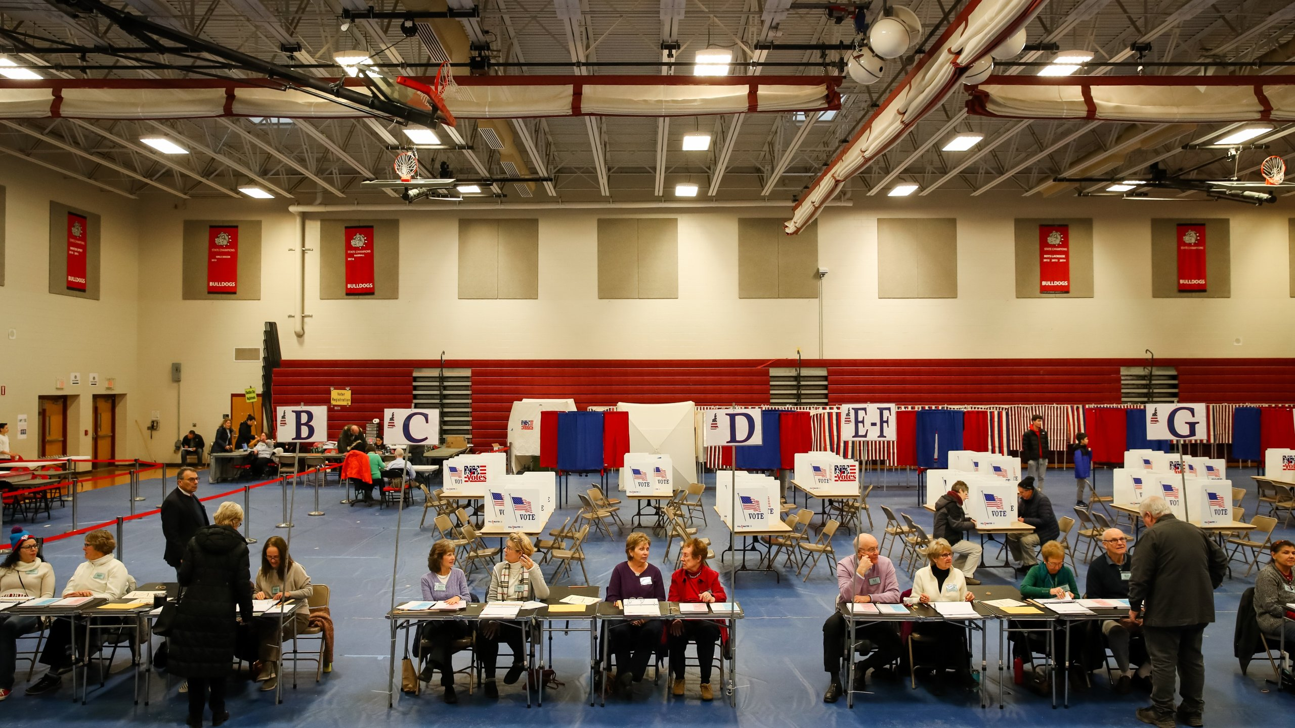 Poll workers wait for voters to check in at Bedford High School during the New Hampshire primary on Feb. 11, 2020 in Bedford, New Hampshire. (Credit: Matthew Cavanaugh/Getty Images)