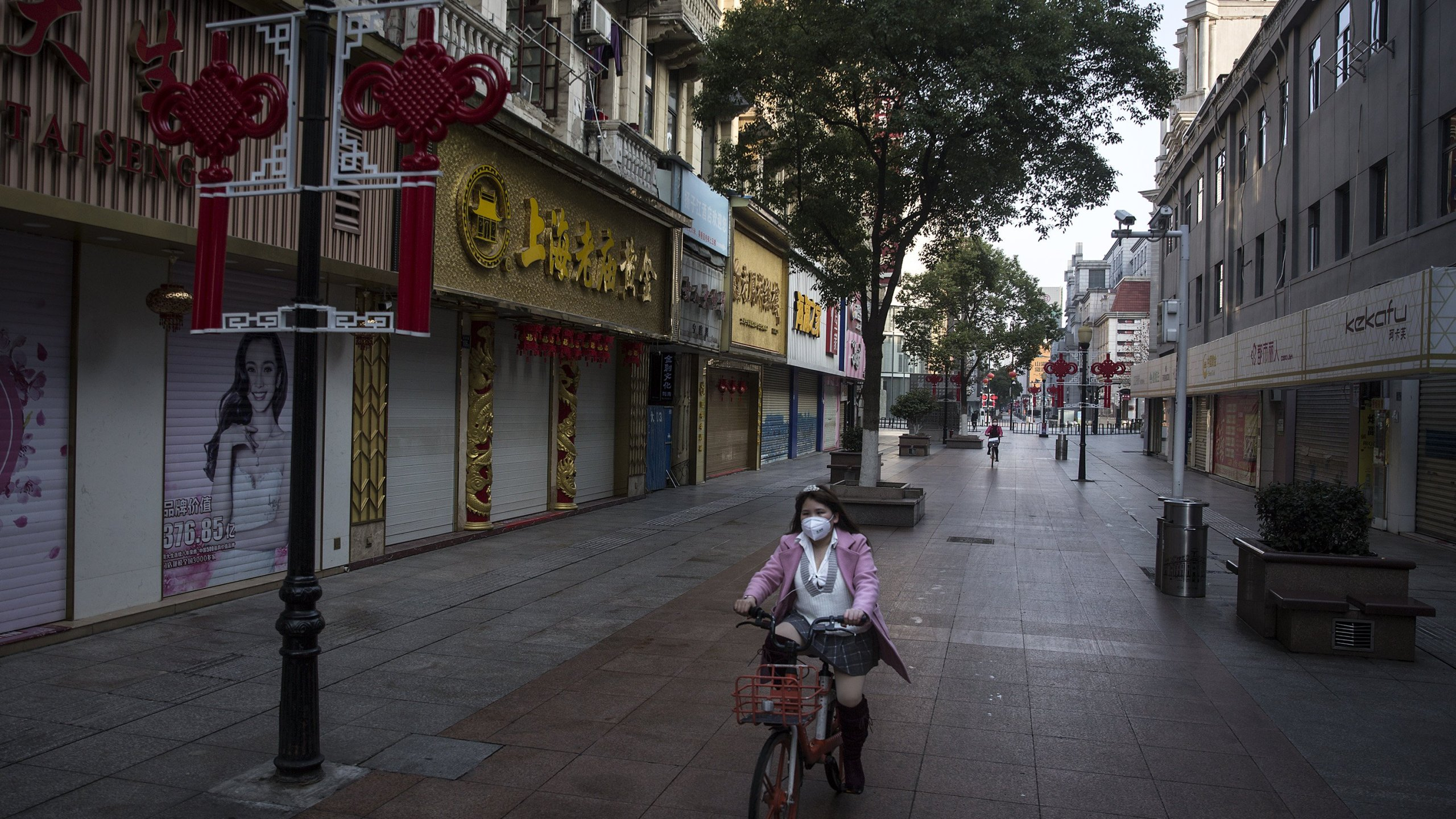 A women wears a protective mask as she cycles past empty businesses on a street in Wuhan, Hubei province, China, on Feb. 13, 2020. Flights, trains and public transport including buses, subway and ferry services have been closed for 22 days. (Credit: Stringe/Getty Images)