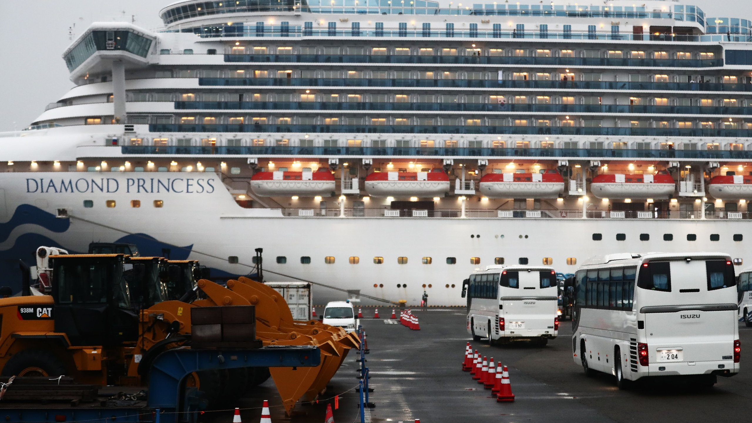 Two buses arrive next to the Diamond Princess cruise ship, with people quarantined onboard due to fears of the new coronavirus, at the Daikaku Pier Cruise Terminal in Yokohama port on Feb.16, 2020.(Credit: BEHROUZ MEHRI/AFP via Getty Images)