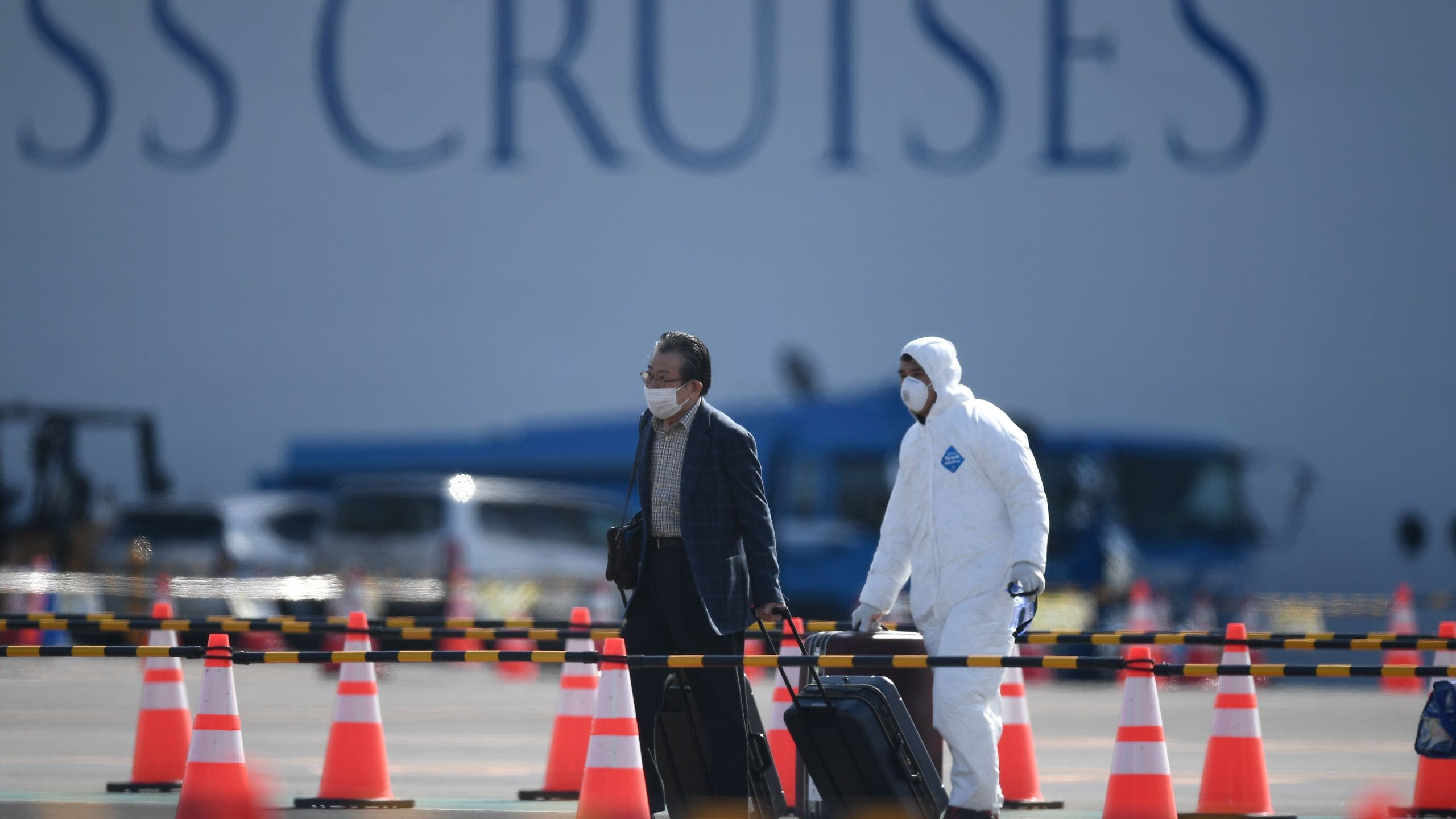 A passenger disembarks from the Diamond Princess cruise ship at the Daikoku Pier Cruise Terminal in Yokohama on Feb. 19, 2020. (Credit: CHARLY TRIBALLEAU/AFP via Getty Images)