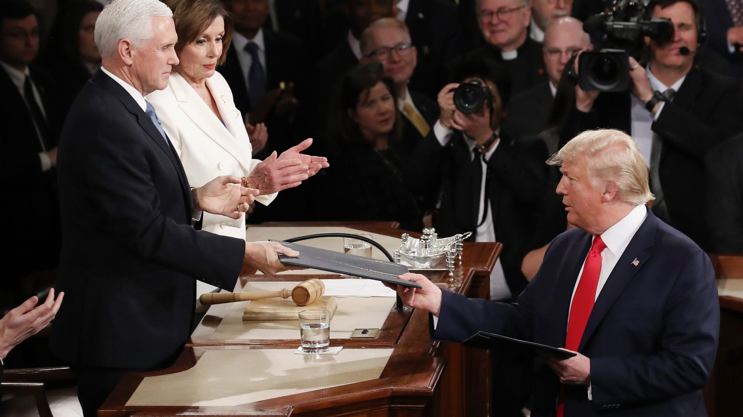 President Donald Trump hands Vice President Mike Pence a copy of his State of the Union speech before the address on Feb. 4, 2020. (Credit: Drew Angerer / Getty Images)