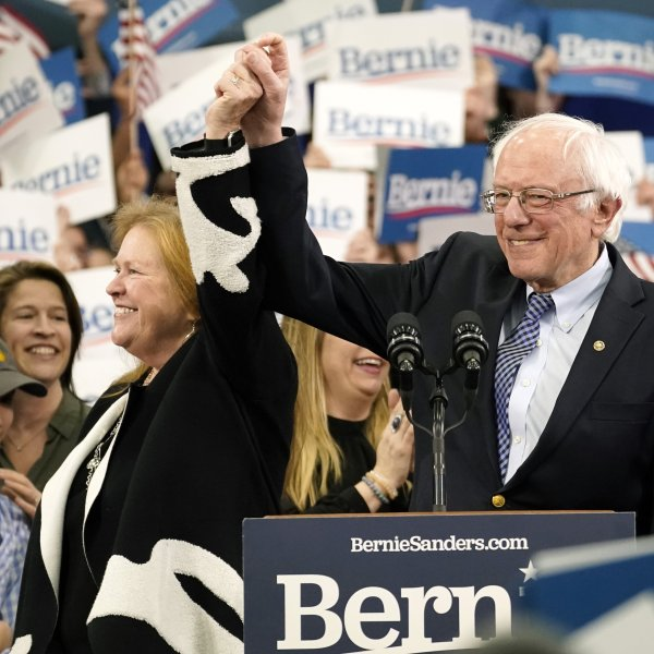 Democratic presidential candidate Sen. Bernie Sanders holds the hand of his spouse Jane O'Meara Sanders as he takes the stage during a primary night event in Manchester, New Hampshire on Feb. 11, 2020. (Credit: Drew Angerer / Getty Images)