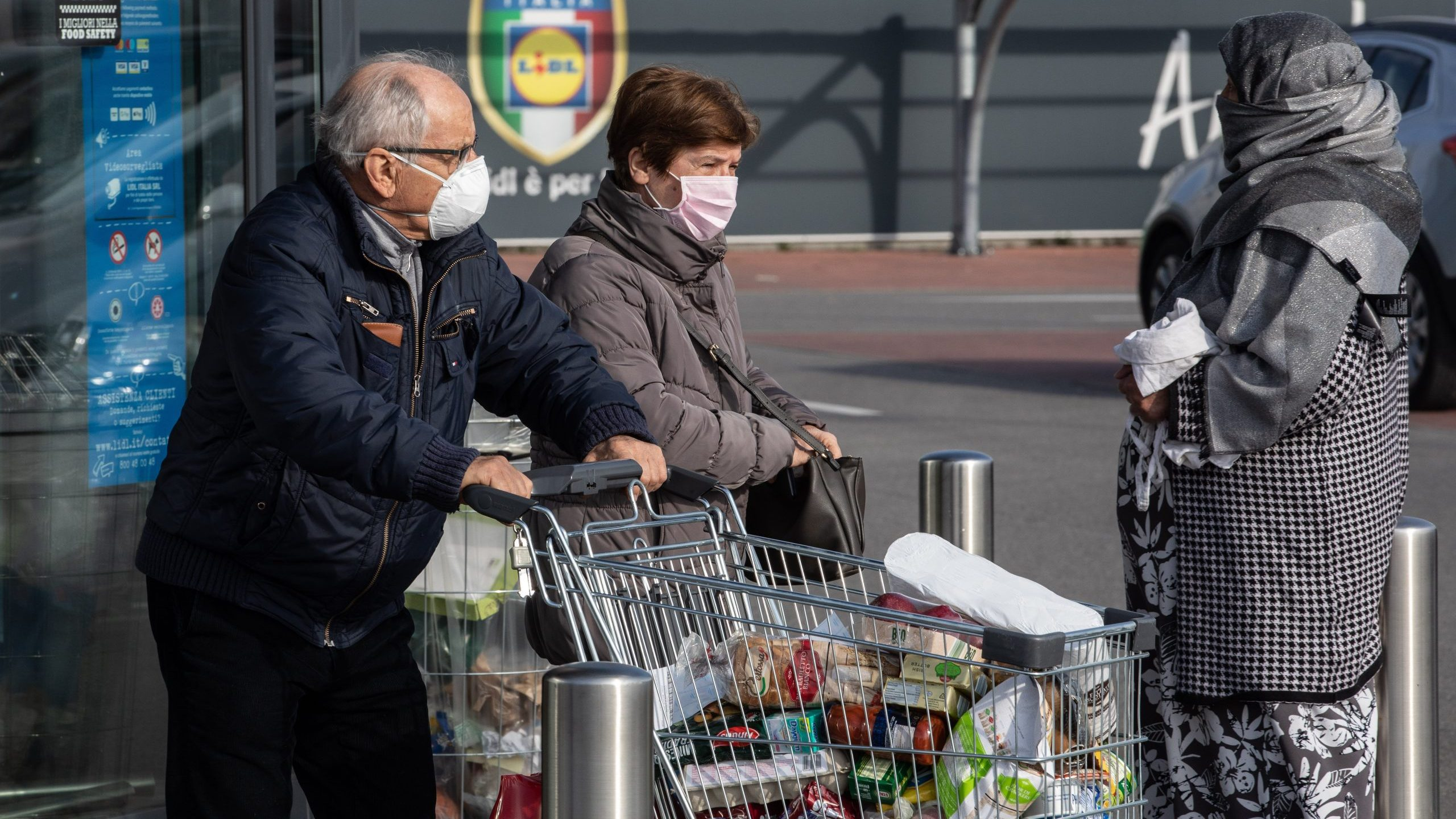 A couple wearing respiratory masks push a trolley loaded with foodstuffs after having been given a 10-minute access to shop on February 23, 2020 in Casalpusterlengo, south-west Milan, Italy. (Credit: Emanuele Cremaschi/Getty Images)