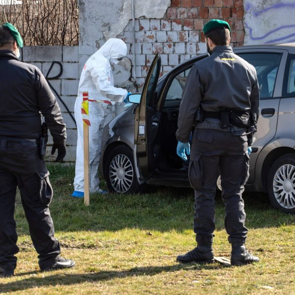 A rescue worker wearing a protective suit checks on a man who tried to reach a hospital driving his own car but was eventually stopped by Italian Guardia di Finanza officers at a road block on Feb. 24, 2020, in Italy. (Credit: Emanuele Cremaschi/Getty Images)