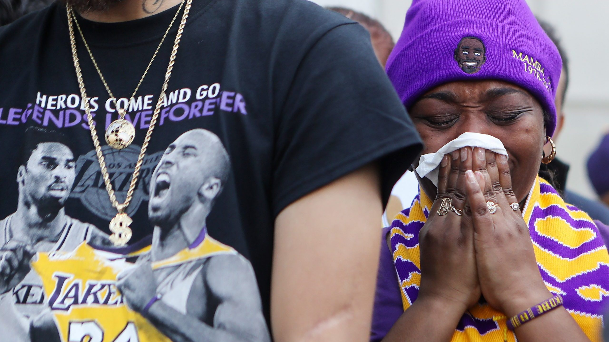 A fan becomes emotional while watching a live broadcast of Kobe and Gianna Bryant's memorial service on a fan's iPad outside the Staples Center on Feb. 24, 2020. (Credit: Mario Tama / Getty Images)
