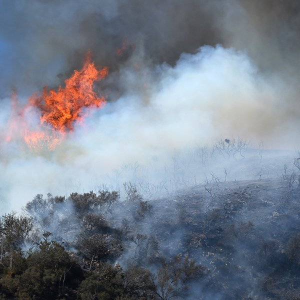 Flames, smoke and scorched earth are seen as a flare up breaks a containment line at the Powerhouse Fire, near Lake Hughes, California, approximately 66 miles north of Los Angeles on June 3, 2013. (Credit: ROBYN BECK/AFP via Getty Images)