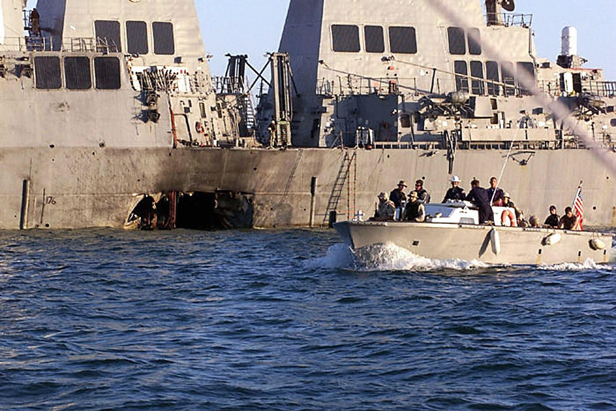This US Navy file photo shows security personnel patrolling past the damaged USS Cole 18 October 2000 following the 12 October 2000 terrorist bombing attack on the ship in Aden, Yemen. (Credit: LYLE G. BECKER/AFP via Getty Images)