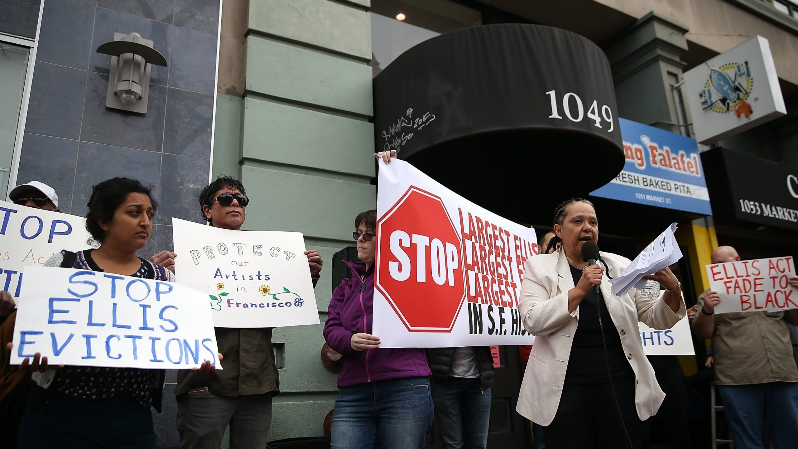 Activists and tenants of 1049 Market Street hold signs as they stage a protest against the landlord's attempts to evict them from the building on March 8, 2016, in San Francisco. (Credit: Justin Sullivan/Getty Images)
