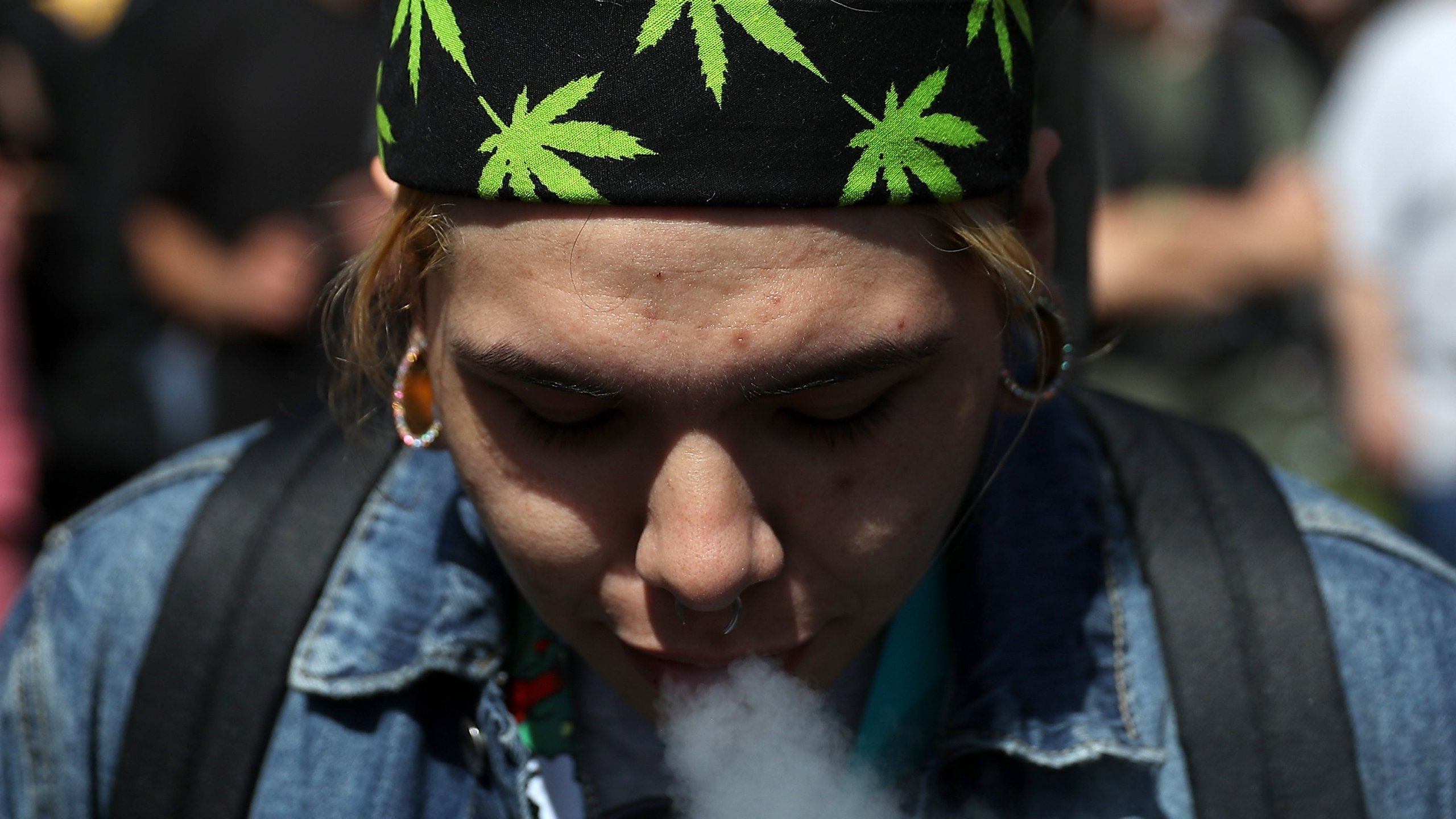 A marijuana user blows smoke after taking a hit from a bong during a 420 Day celebration on 'Hippie Hill' in Golden Gate Park on April 20, 2018, in San Francisco. (Credit: Justin Sullivan/Getty Images)