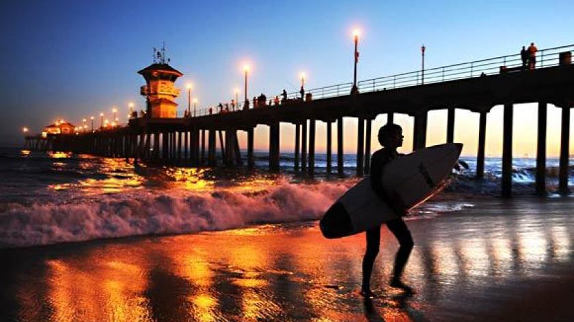 A surfer leaves the water at Huntington Beach Pier. Early Friday, a tsunami alarm sounded across the city, but officials said it was made in error.(Credit: Wally Skalij / Los Angeles Times)