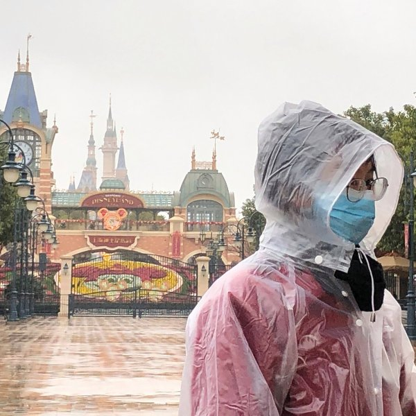 A Disney employee stands in front of the gates of the Shanghai Disney Resort. (Credit: Fut Ting/AP/Shutterstock via CNN Wire)
