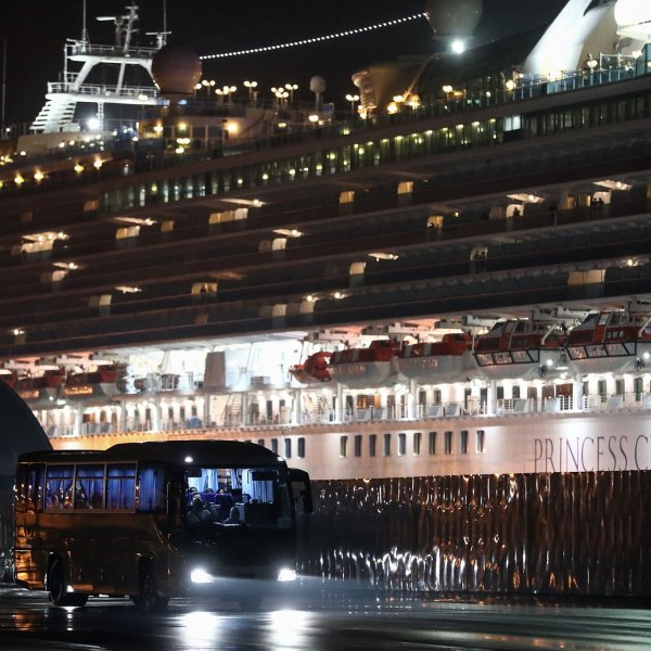 A bus carrying U.S. citizens leaves the Daikaku Pier Cruise Terminal in Yokohama port, next to the Diamond Princess cruise ship, with people quarantined onboard due to fears of the new COVID-19 coronavirus, on Feb. 17, 2020. (Credit: Behrouz Mehri/AFP/Getty Images)