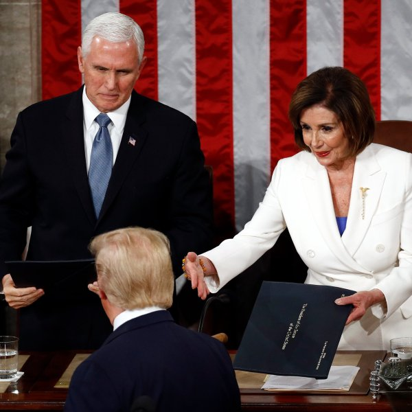 President Donald Trump hands copies of his speech to House Speaker Nancy Pelosi and Vice President Mike Pence as he delivers his State of the Union address on Capitol Hill on Feb. 4, 2020. (Credit: AP Photo/Patrick Semansky via CNN)
