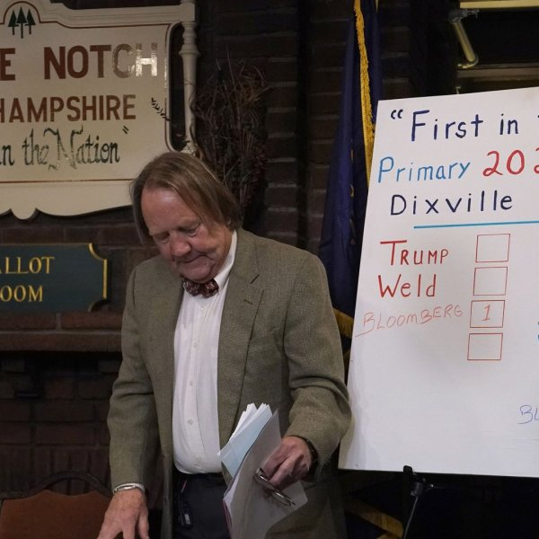 Town moderator Tom Tillotson walks past the results board after midnight voting at the Hale House at the legendary Balsams Resort in the New Hampshire hamlet of Dixville Notch February 11, 2020, where midnight voting took place on the day of the state's first-in-the-nation primary. (Credit: Timothy A. Clary/AFP via Getty Images)