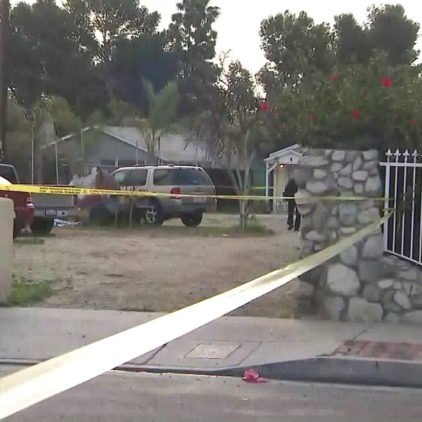 Caution tape surrounds a Pacoima home on Feb. 22, 2020 after a shooting left one person dead. (Credit: KTLA)