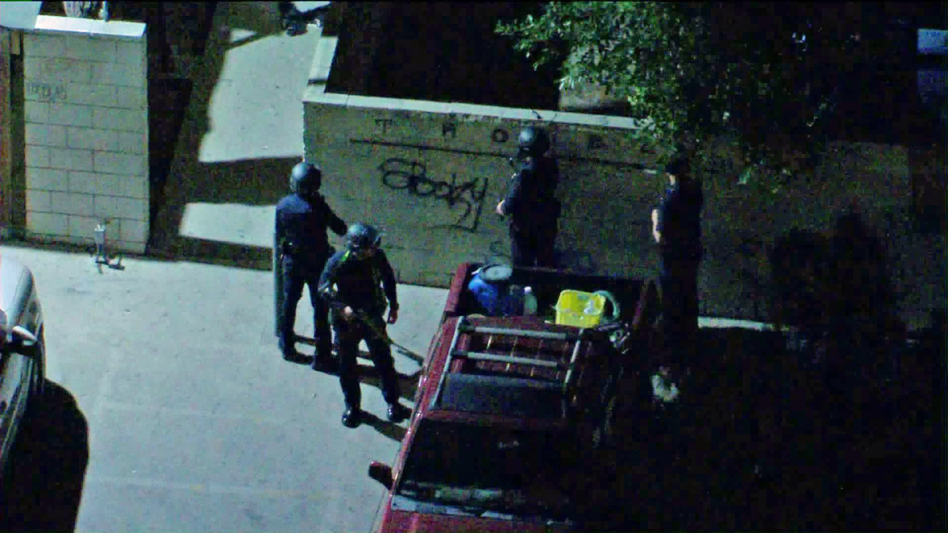 Los Angeles police officers search for a homicide suspect after a pursuit came to an end in Panorama City on Feb. 24, 2020. (Credit: KTLA)