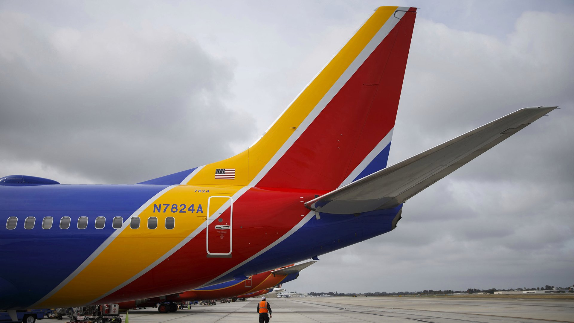 A Southwest Airlines Co. employee walks underneath the tail of a Boeing Co. 737 aircraft on the tarmac at John Wayne Airport (SNA) in Santa Ana, California, U.S., on Thursday, April 14, 2016. (Credit: Patrick T. Fallon/Bloomberg via Getty Images)