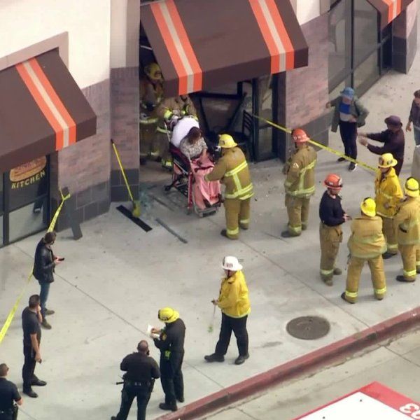 A patient is seen on a stretcher after a vehicle crashed into the Pita Kitchen Restaurant in Tarzana on Feb. 21, 2020. (Credit: KTLA)