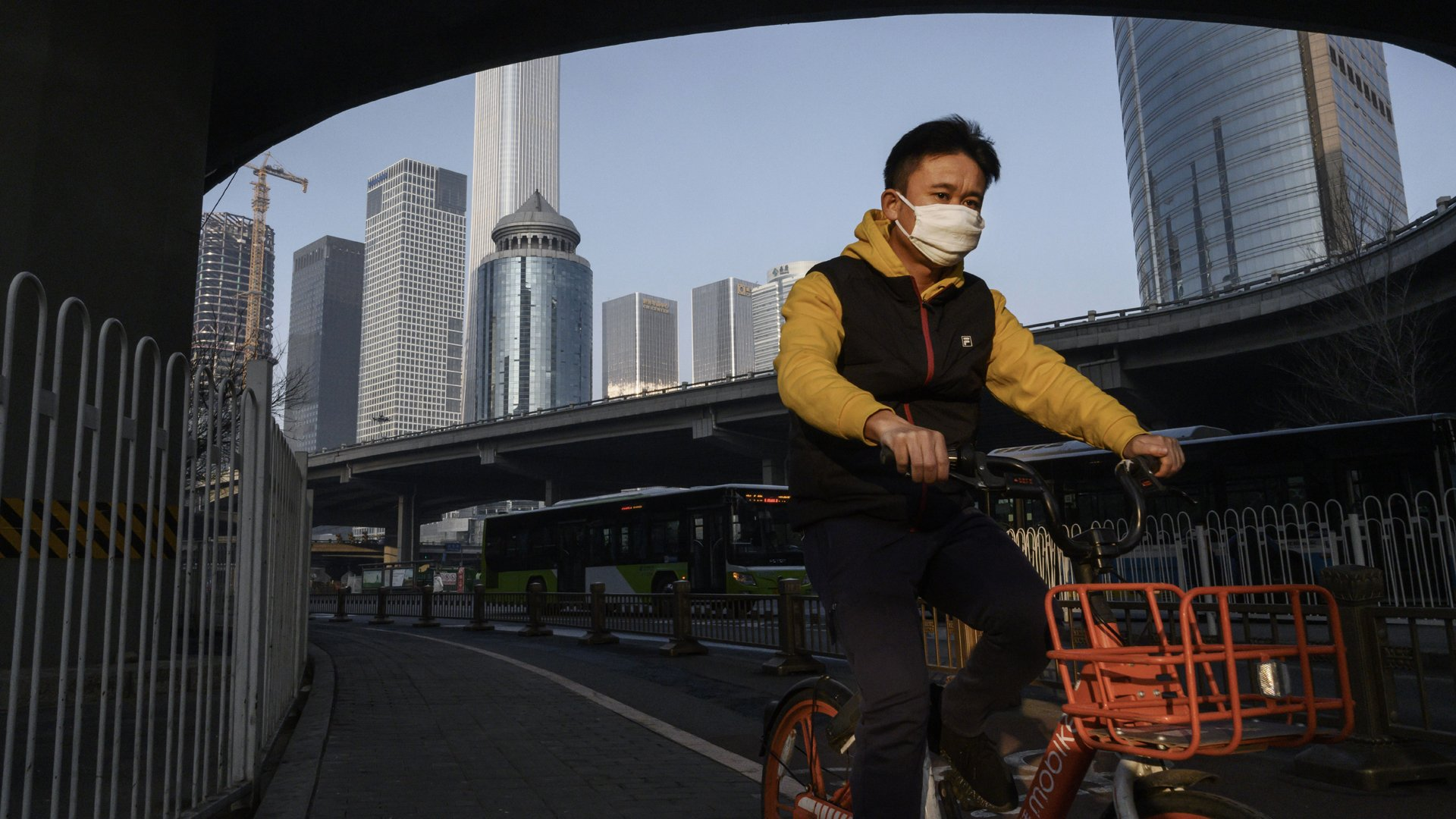 A Chinese man wears a protective mask as he cycles on a quiet road during the usual rush hour period on February 10, 2020 in Beijing, China. (Credit: Kevin Frayer/Getty Images)
