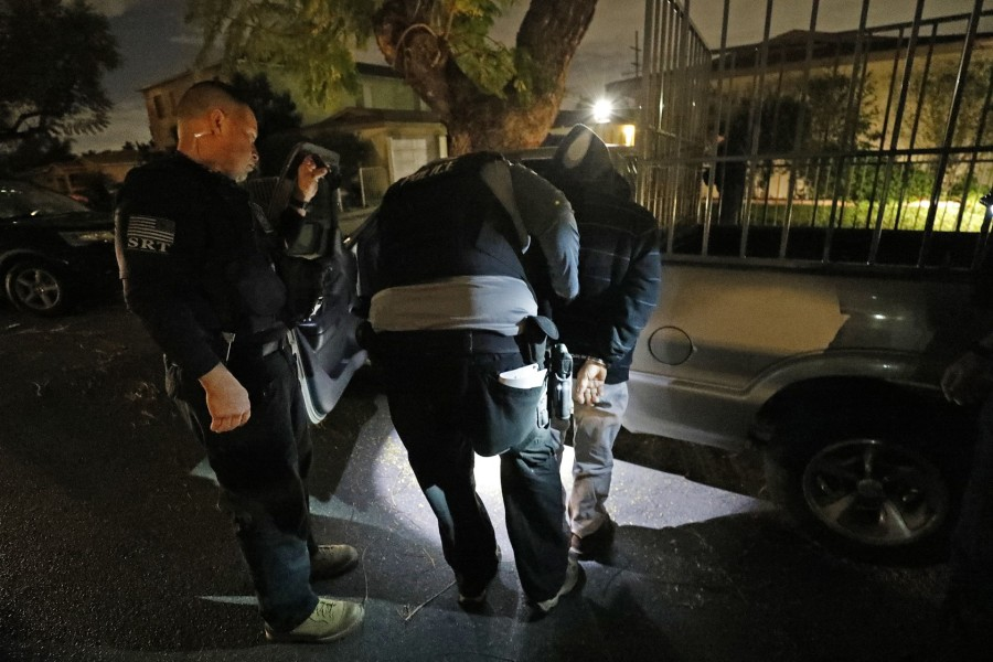 David A. Marin, left, a director of enforcement and removal operations with ICE, looks on as a man is taken into custody before dawn on March 16, 2020. (Al Seib/Los Angeles Times)